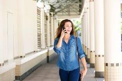 Счастливая молодая женщина идя и говоря на мобильном телефоне Стоковые Фотографии RF