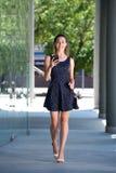 Счастливая молодая женщина идя снаружи с мобильным телефоном Стоковое Изображение RF