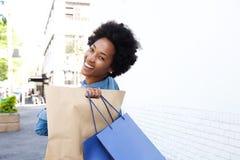 Счастливая молодая женщина идя int он город с хозяйственными сумками Стоковые Фото