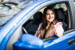 Счастливая молодая женщина красоты показывает большой палец руки от автомобиля стоковое изображение rf