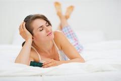 Счастливая молодая женщина кладя в кровать с пакетом волдыря пилюлек Стоковое Изображение RF