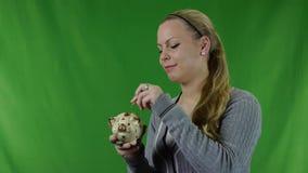 Счастливая молодая женщина кладя монетку в копилку против зеленого экрана. акции видеоматериалы