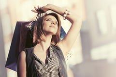 Счастливая молодая женщина моды с хозяйственными сумками на улице города стоковые фото