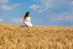 Счастливая молодая женщина наслаждаясь жизнью в золотом пшеничном поле Стоковая Фотография RF