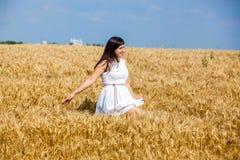 Счастливая молодая женщина наслаждаясь жизнью в золотом пшеничном поле Стоковое Изображение
