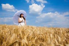 Счастливая молодая женщина наслаждаясь жизнью в золотом пшеничном поле Стоковые Изображения