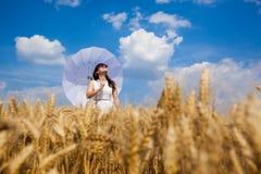 Счастливая молодая женщина наслаждаясь жизнью в золотом пшеничном поле Стоковое фото RF