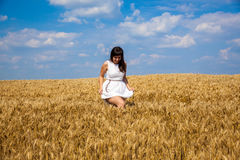 Счастливая молодая женщина наслаждаясь жизнью в золотом пшеничном поле Стоковое Фото