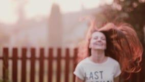 Счастливая молодая женщина наслаждаясь природой, поворачивающ, имеющ потеху, усмехающся, скакать утехи Волосы дамы s порхают на в