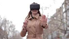 Счастливая молодая женщина на улице в бежевом пальто играя имеющ стекла виртуального пространства шлемофона виртуальной реальност видеоматериал