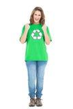 Счастливая молодая женщина нося зеленую рубашку с рециркулировать символ стоковое фото