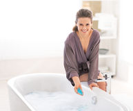 Счастливая молодая женщина добавляя соль для принятия ванны в ванне стоковая фотография
