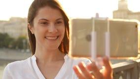 Счастливая молодая женщина ослабляя outdoors Красивая девушка делая selfie на smartphone Солнце лета светя акции видеоматериалы