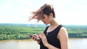 Счастливая молодая женщина посылая sms, отправляя СМС в парке волосы дуя в ветре сток-видео