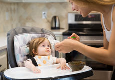 Счастливая молодая женщина подавая милая маленькая девочка с ложкой Стоковое Фото