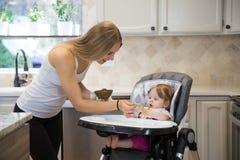 Счастливая молодая женщина подавая милая маленькая девочка с ложкой Стоковая Фотография RF