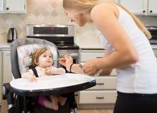 Счастливая молодая женщина подавая милая маленькая девочка с ложкой Стоковые Фотографии RF