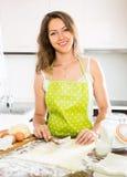 Счастливая молодая женщина подготавливая торты стоковые изображения