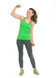 Счастливая молодая женщина пригодности при гантели показывая бицепсы Стоковое Фото