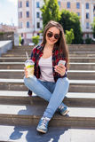 Счастливая молодая женщина при свежая чашка сидя на лестницах и используя ее smartphone Стоковое фото RF