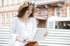 Счастливая молодая женщина работая при компьтер-книжка сидя на стенде Стоковое Изображение RF