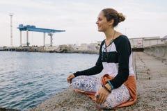 Счастливая молодая женщина сидя на представлении йоги на док и смотря вперед Стоковые Изображения RF