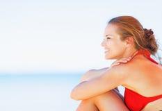 Счастливая молодая женщина сидя на пляже и смотря на космосе экземпляра стоковые фотографии rf