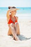 Счастливая молодая женщина сидя на пляже и смотря на космосе экземпляра стоковое изображение rf
