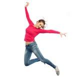Счастливая молодая женщина скача в воздух или танцевать Стоковые Фото