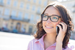 Счастливая молодая женщина смотря отсутствующий пока использующ умный телефон на солнечный день Стоковая Фотография RF