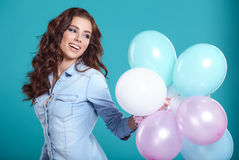 Счастливая молодая женщина стоя над голубой стеной и держа воздушные шары стоковая фотография