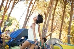 Счастливая молодая женщина стоя при друзья сидя в предпосылке Стоковые Изображения RF