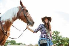 Счастливая молодая женщина с ее лошадью на ферме Стоковое Изображение RF