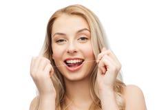 Счастливая молодая женщина с зубами чистки зубоврачебной зубочистки Стоковые Фотографии RF