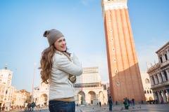 Счастливая молодая женщина указывая на колокольню St отметит базилику Стоковое Изображение