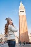 Счастливая молодая женщина указывая на колокольню St отметит базилику Стоковое фото RF