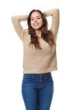 Счастливая молодая женщина усмехаясь с руками в волосах Стоковое фото RF