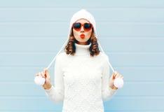Счастливая молодая женщина дуя красные губы делает воздух расцеловать нося солнечные очки формы сердца, связанную шляпу, свитер н Стоковое Фото