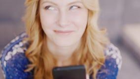 Счастливая молодая женщина читая сообщение на вашем мобильном телефоне Она счастлива, усмехающся, эмоциональная реакция сток-видео
