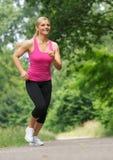 Счастливая молодая женщина jogging outdoors Стоковые Изображения
