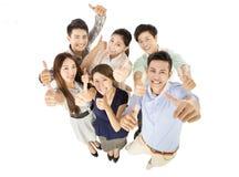 Счастливая молодая команда дела с большими пальцами руки вверх показывать стоковые фотографии rf