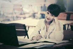 Счастливая молодая коммерсантка с компьтер-книжкой на кафе тротуара стоковое фото