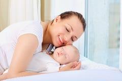 Счастливая молодая мать и ее младенец на окне Стоковое Изображение