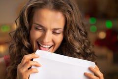 Счастливая молодая домохозяйка лижа конверт стоковая фотография