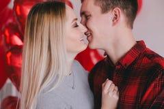 Счастливая молодая пара в влюбленности представляя с красным сердцем раздувает Стоковые Изображения RF