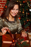 Счастливая молодая подарочная коробка отверстия женщины брюнет около рождественской елки Стоковая Фотография RF