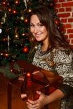 Счастливая молодая подарочная коробка отверстия женщины брюнет около рождественской елки Стоковое Изображение
