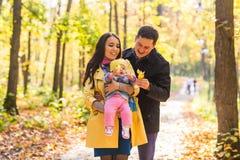 Счастливая молодая семья в парке осени outdoors на солнечный день Мать, отец и их маленький ребёнок идут внутри Стоковая Фотография