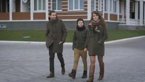 Счастливая молодая семья в теплой одежде идет совместно на улицу смеясь над и говоря Отец и мать акции видеоматериалы