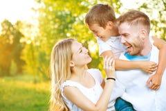 Счастливая молодая семья имея потеху outdoors